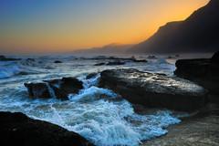 波涛汹涌的海浪与静谧的大山和缓缓下山的夕阳